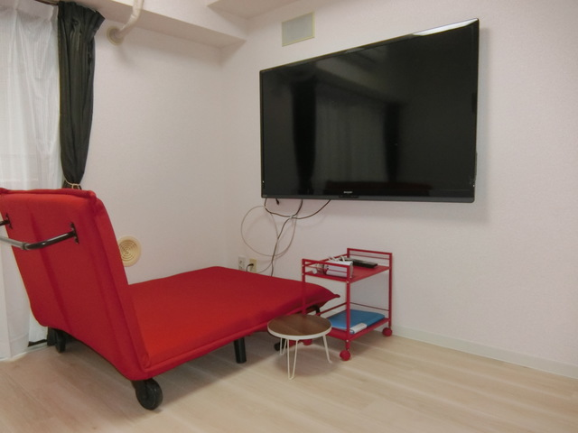 60インチの壁掛けTVと折りたたみが可能なソファベッド付き。